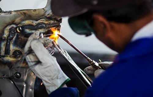 technician using a torch to fix a car