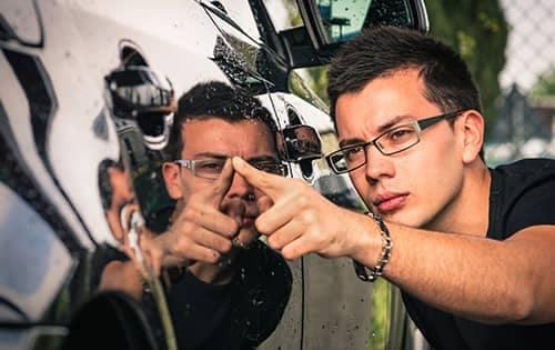 service technician running his finger along a shiny car door