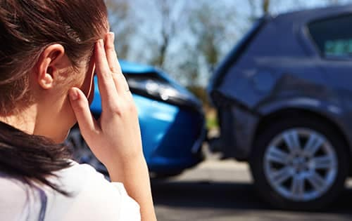 woman holding her head in hands looking over car crash