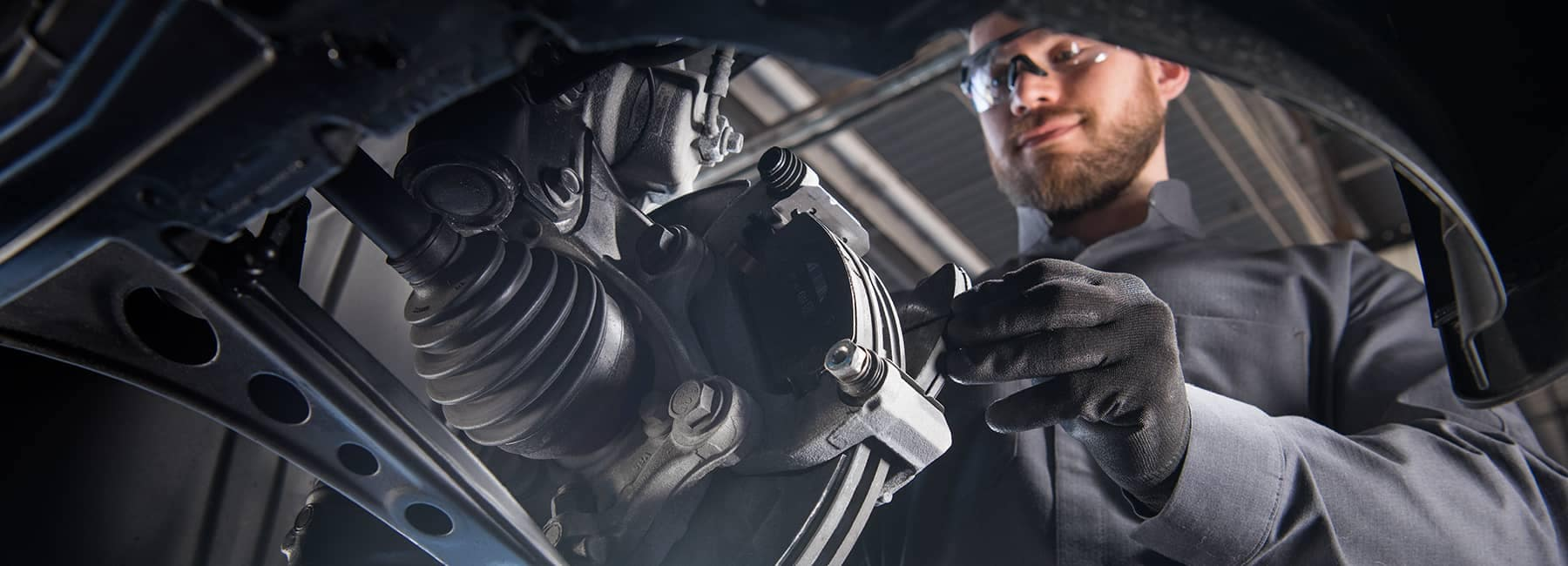 GM service technician with gloves working on rotors