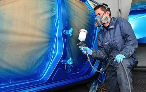 Technician painting car