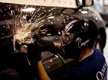 Technician grinding car body