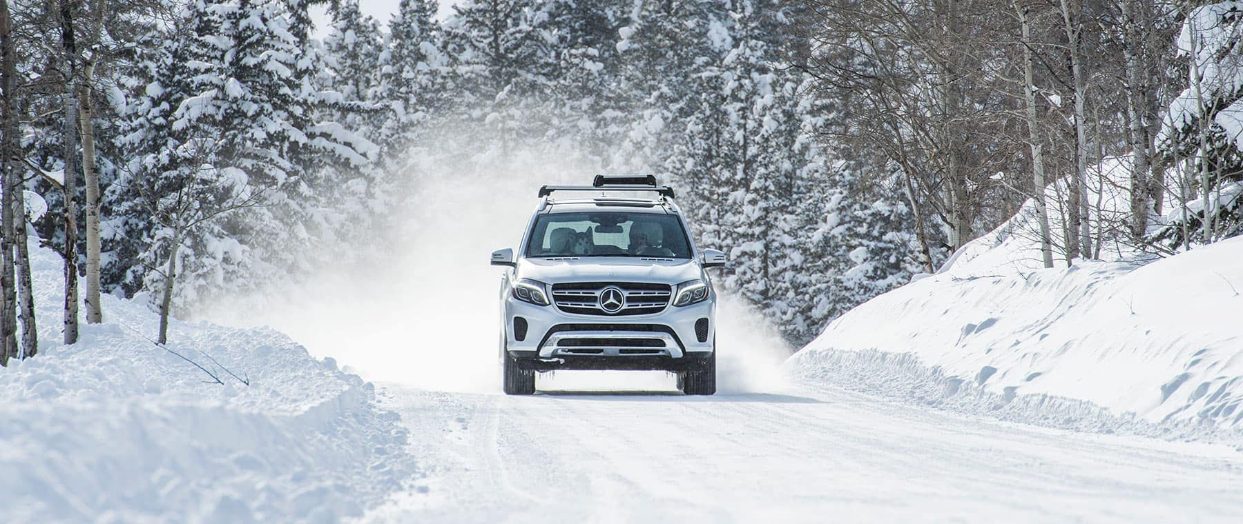 White Mercedes-Benz SUV driving down a road covered in snow