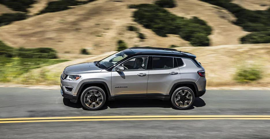 2019 Silver Jeep Compass Limited driving down a road