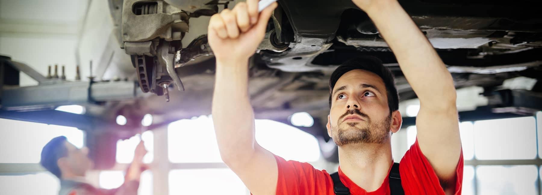 mechanic under car on car rack