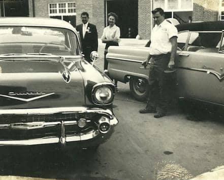 men standing outside two cars