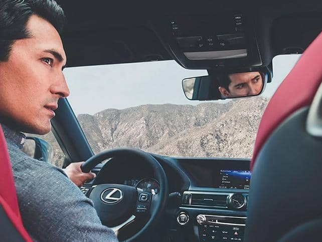 A man sits with his hand at the steering wheel of a Lexus vehicle with a mountain view through the window.