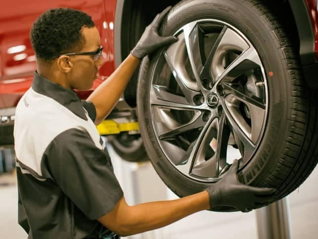 A service rep rotates a tire on a red Lexus.