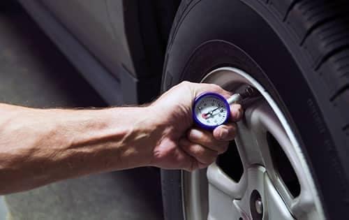 Technician checking tire pressure