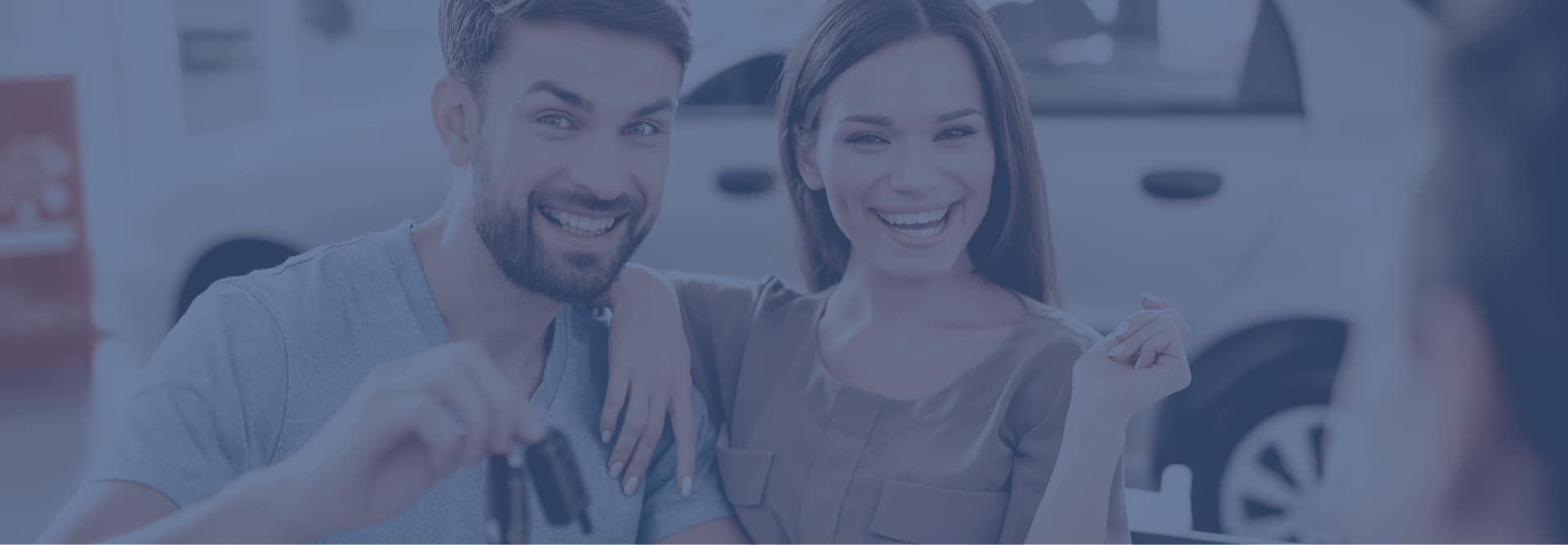 Man and Woman smiling while holding car keys