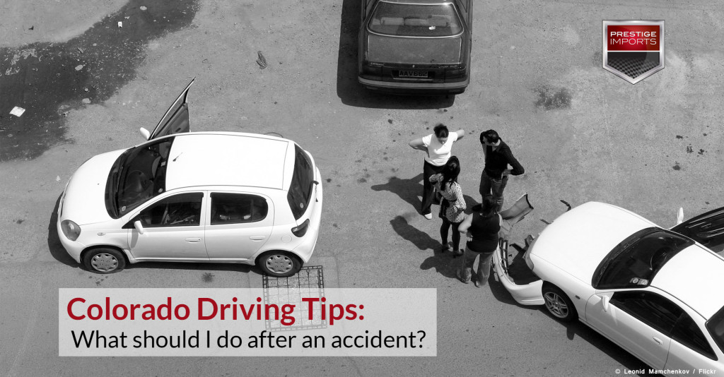 Photo from above of three cars involved in an accident. The drivers are standing in the middle of the frame discussing the incident. Photo used to illustrate the article - Colorado Driving Tips - What should I do after an accident?