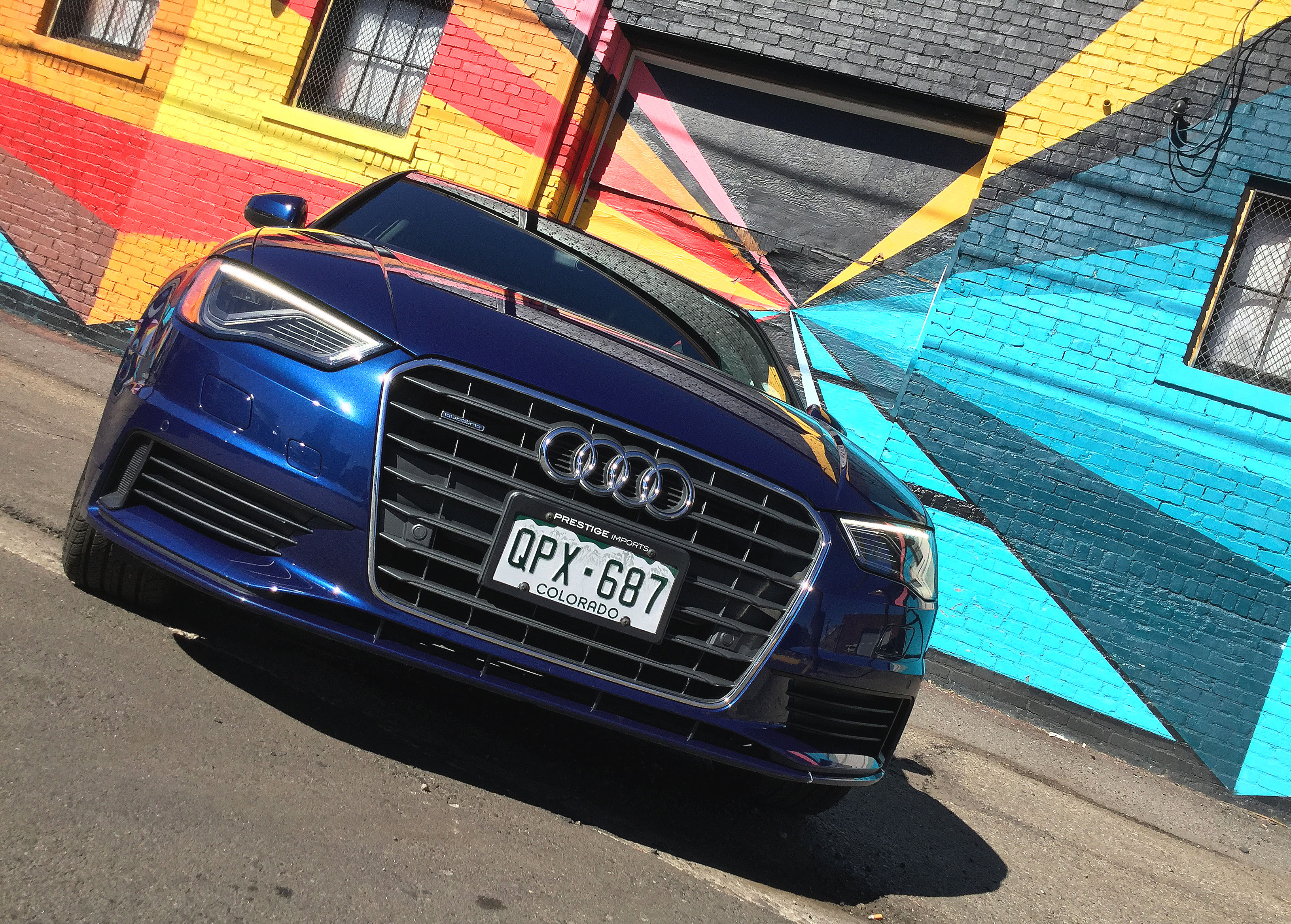 Low angle view of the Audi A3 in front of a colorful mural in Denver's RiNo Art District.