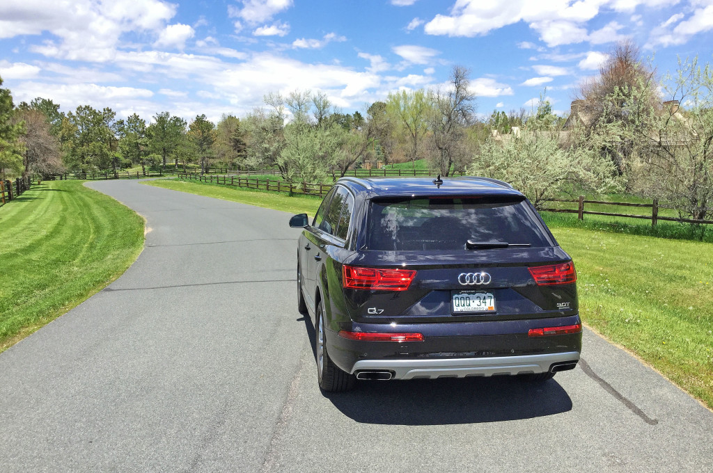 The rear view of an Audi Q7 driving passed some cottonwoods on a winding road in Cherry Hills Village, Colorado.