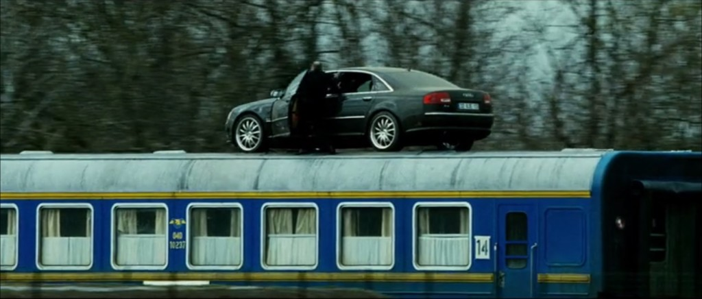 Still image capture from the film Transporter 3 of a 2008 Audi A8 L W12 on the roof of a passenger train.
