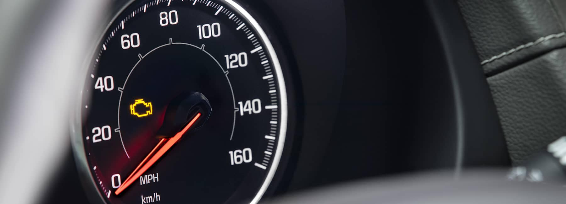 closeup of check engine light in dashboard