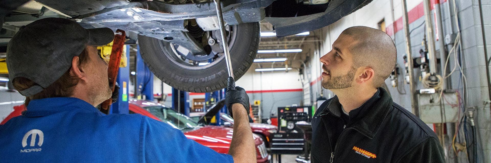 Parts technicians under vehicle