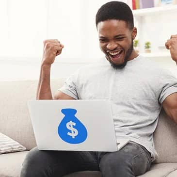 guy celebrating on couch with a money sign on his laptop