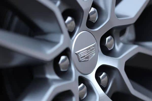 A close up of a Cadillac tire rim.