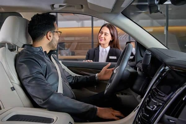 A man sitting in a car talking to a sales rep