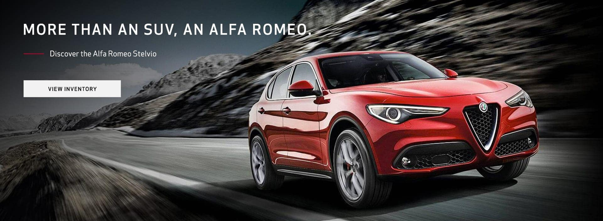 An Alfa Romeo Stelvio driving down a road with a blurred background of mountains.