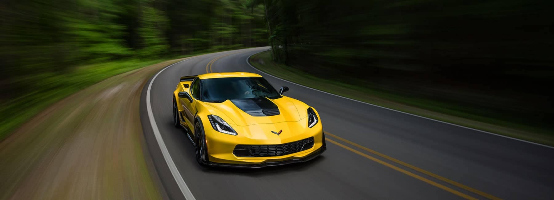 2019 Chevrolet Banner image of a yellow Corvette cruising through a wooded one lane road