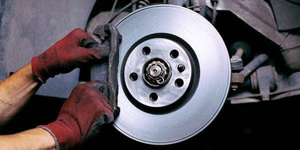 Closeup of a mechanic replacing a brake pad on a car
