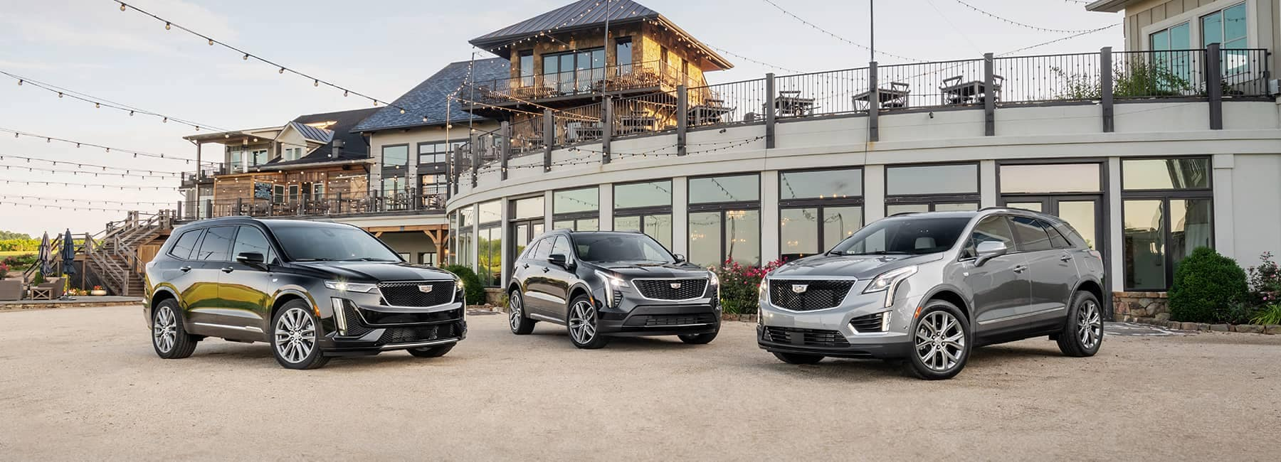 Three Cadillac XT Crossover Models Parked outside of an upscale activity and dining club