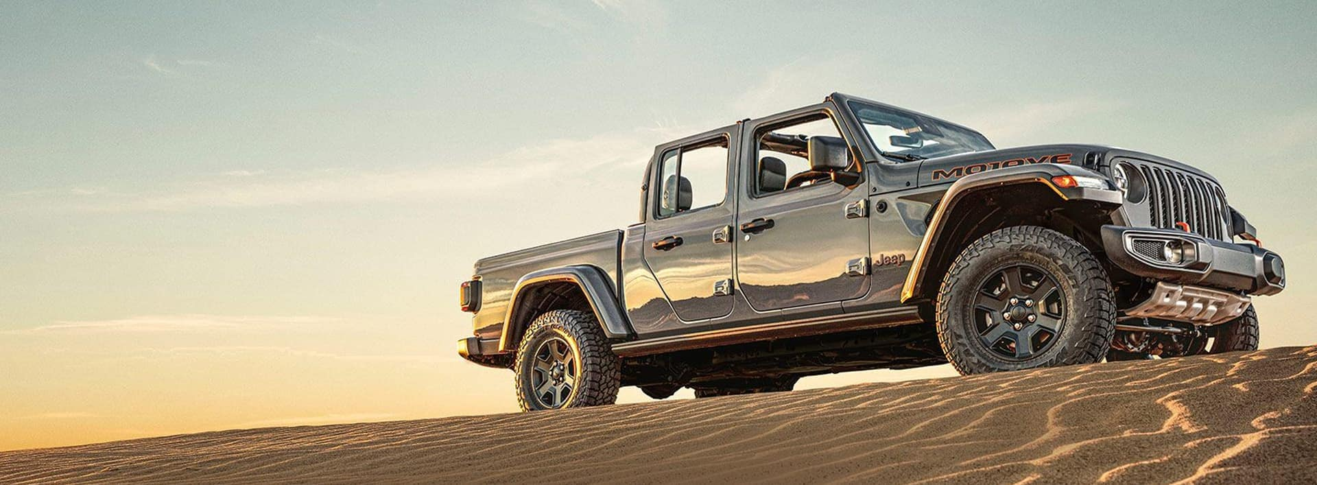 Jeep Gladiator sitting on top of a sand dune
