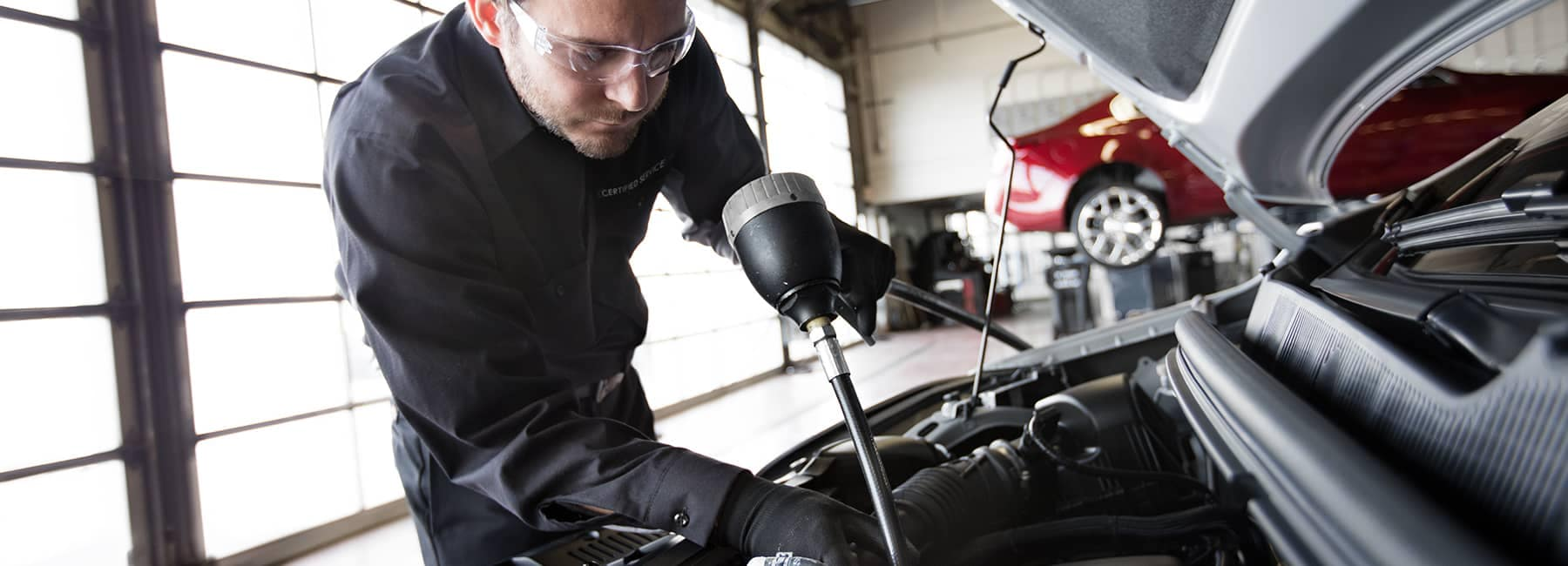 GM Certified Service Technician Working on Engine