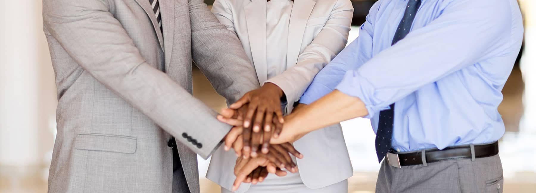 Three Business People with Hands in Middle