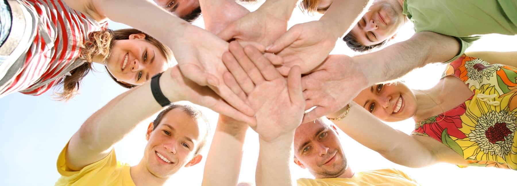 young people place their hands together in a circle