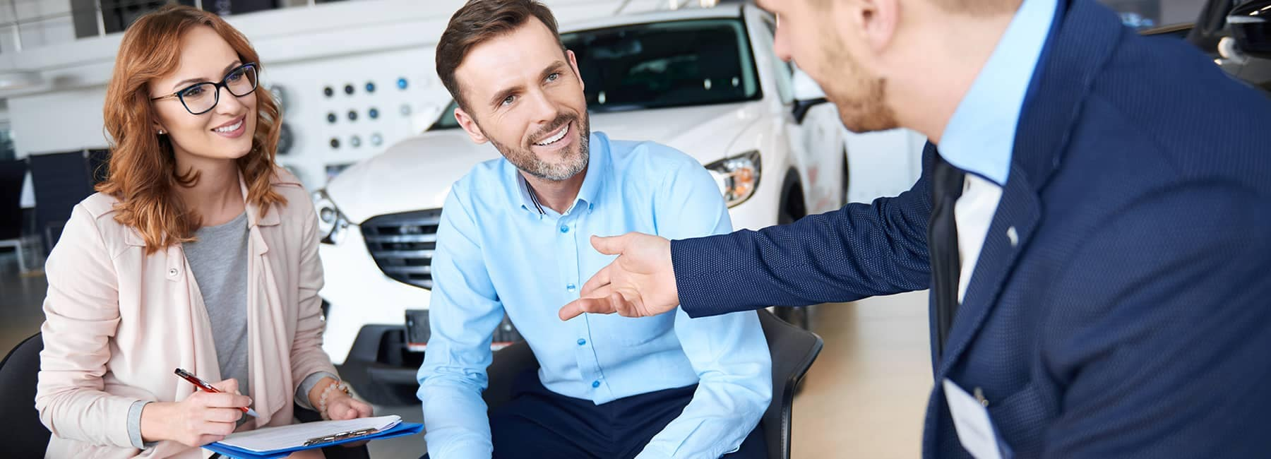 smiling couple talks with car salesman in showroom