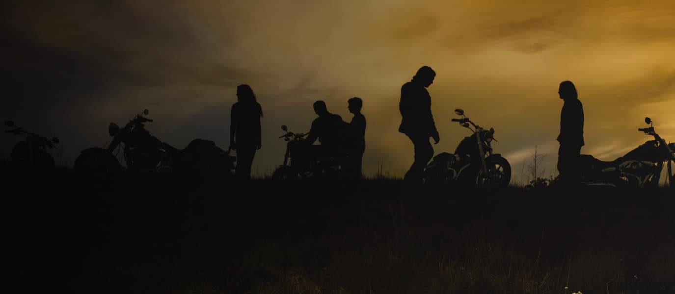 bunch of people standing around motorcycles at dusk
