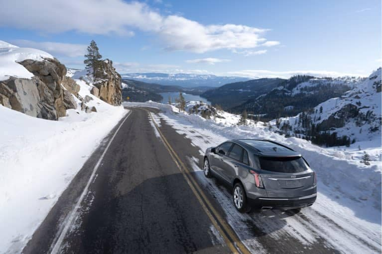 2020 Cadillac XT5 driving down snowy mountain road mobile