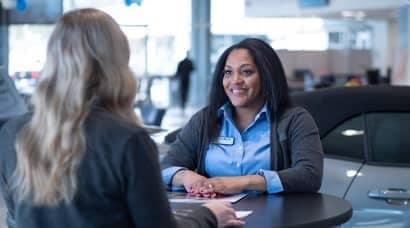 Women speaking to staff inside dealership