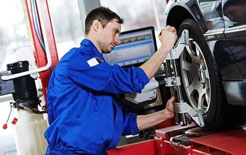 technician aligning tire