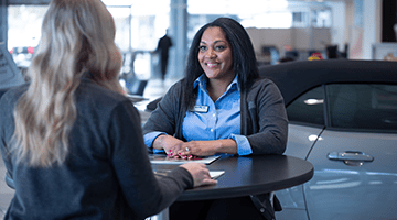 two women sitting across from each other at dealership
