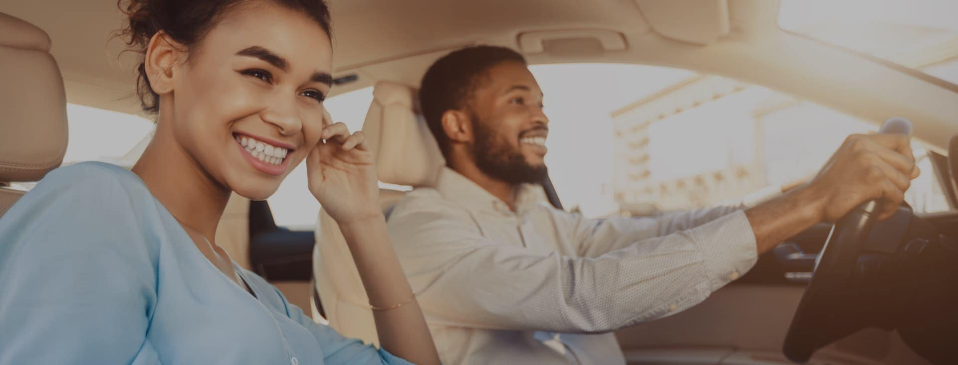 Man and woman happily driving a car