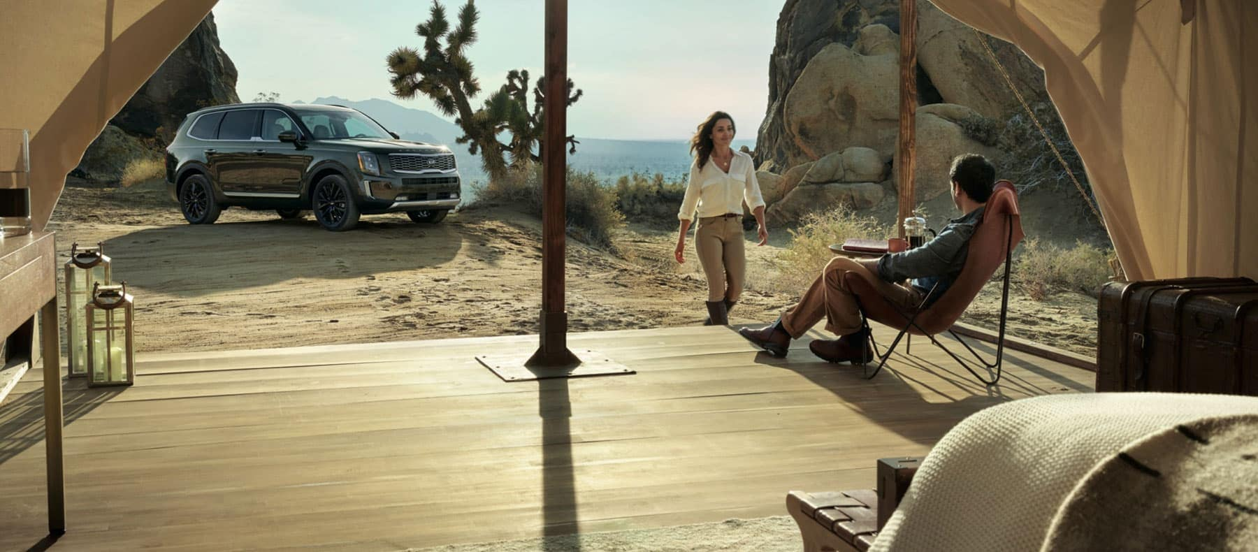 Kia SUV sitting outside a camp site of a man and woman in the desert