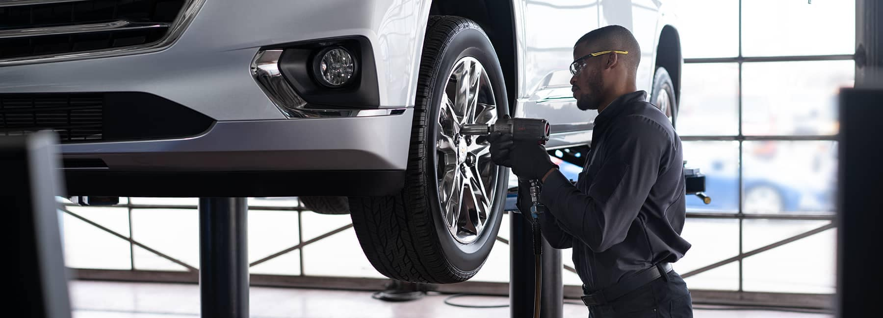 Certified technician tightens bolts on tire