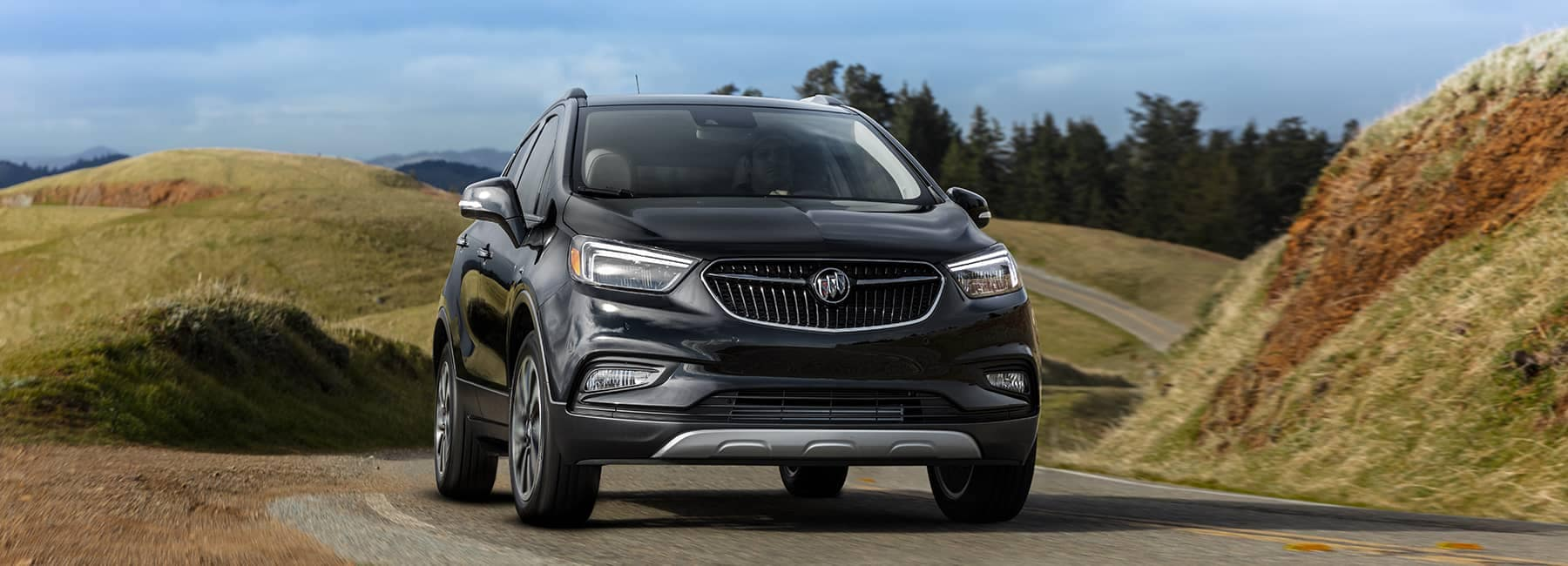 Black 2020 Buick Encore drives country road