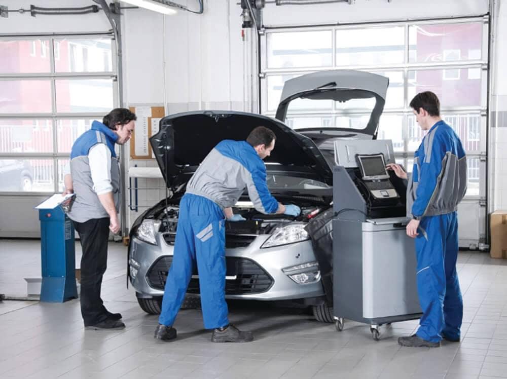 3 mechanics working on car