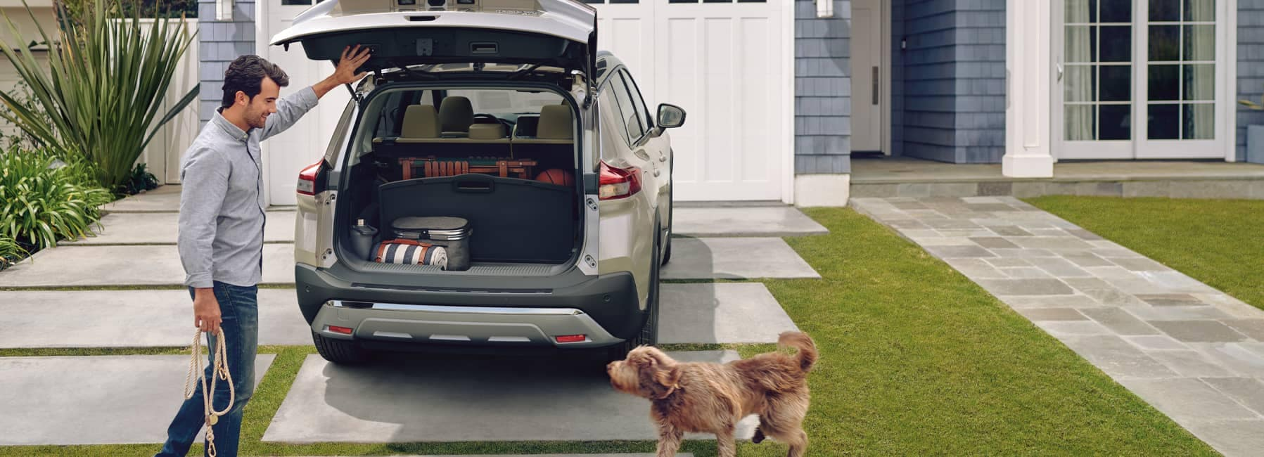 A man and his dog loading up the back of a 2021 Nissan Rogue parked in residential driveway