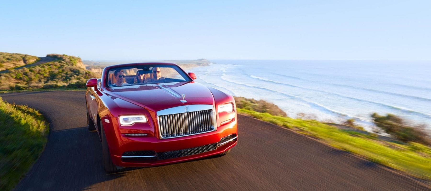 A Rolls-Royce Dawn driving down a road with an ocean view on the background