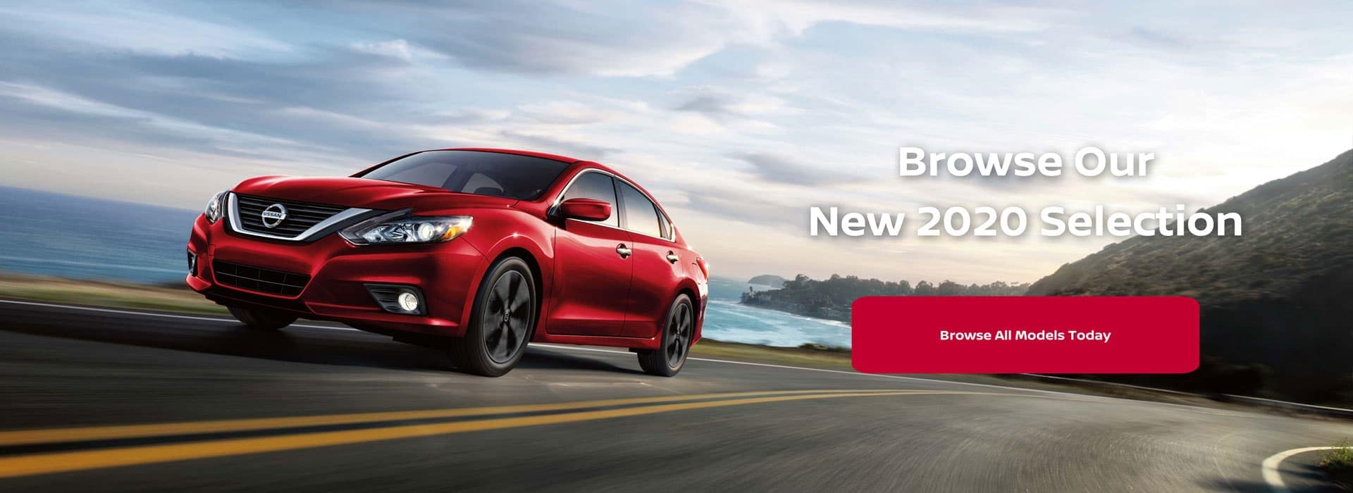Red Nissan sedan driving down a road. Browse our new 2020 selection