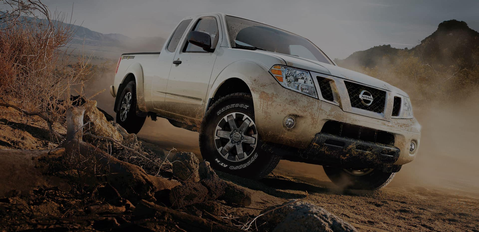 White Nissan Titan driving though the mud