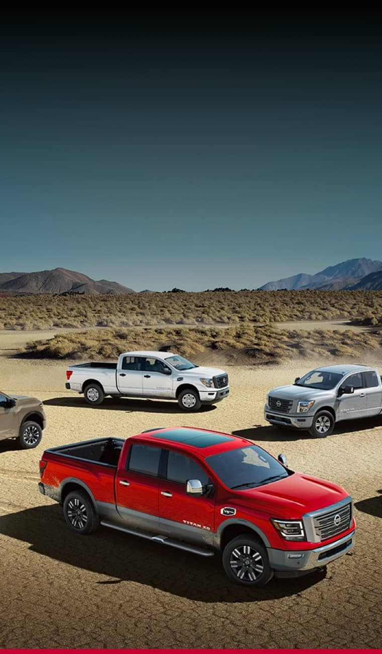 Multiple Nissan pick-up trucks are parked on a desert terrain.