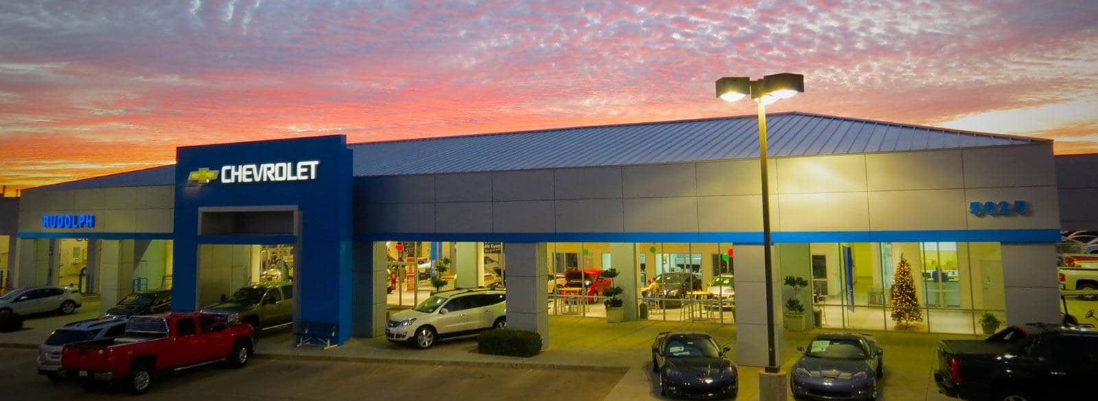 exterior of dealership as sun sets behind the building