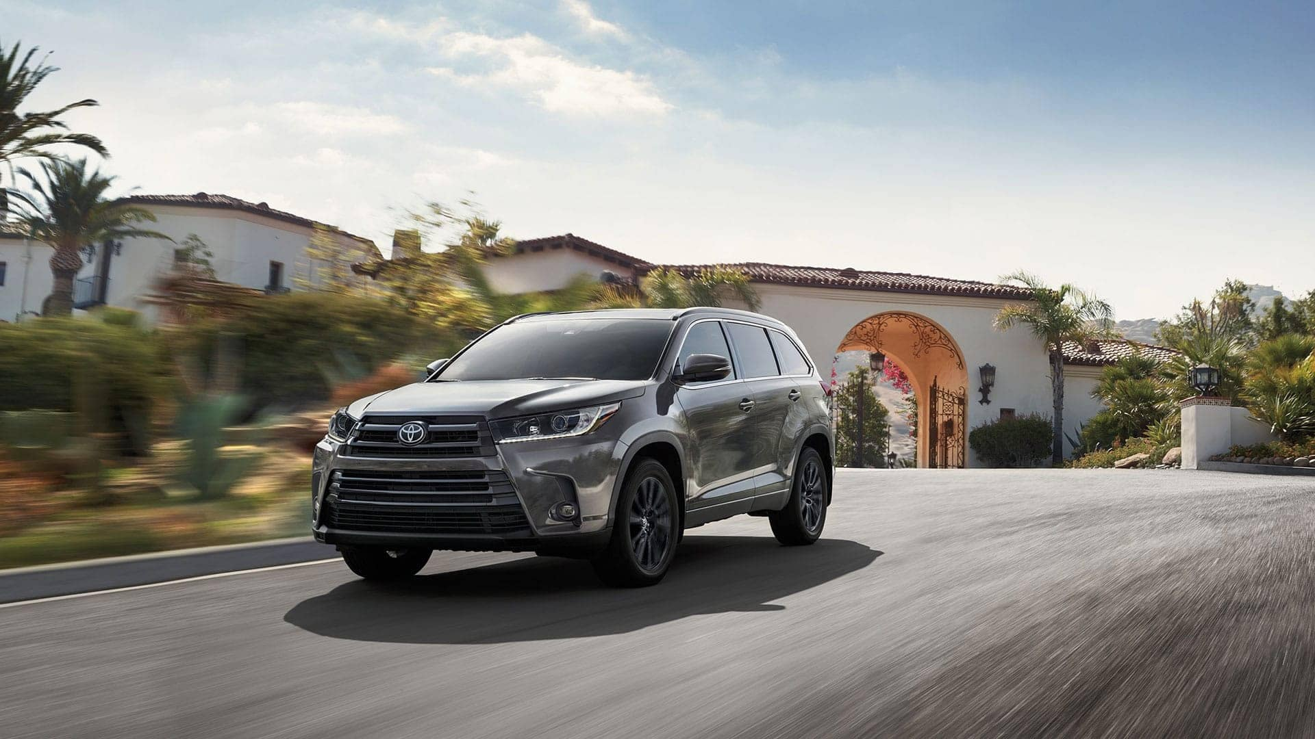 2019 Toyota Highlander driving past adobe house
