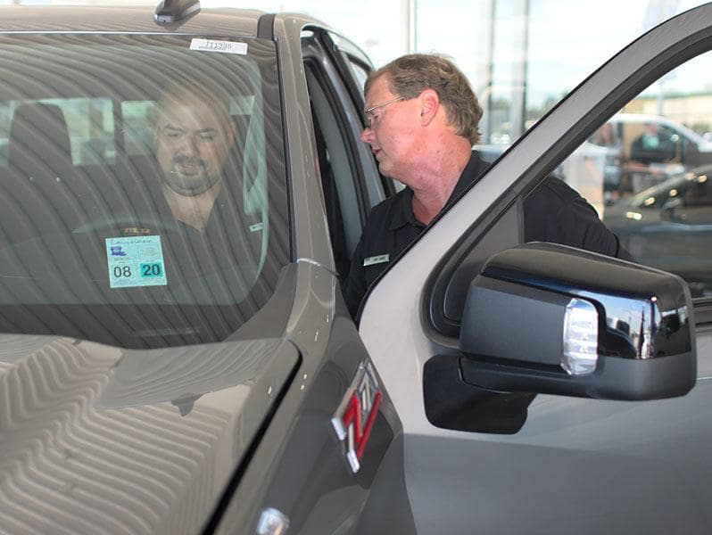 An exterior shot of a customer sitting behind the wheel of a car while a Sales Representative helps out